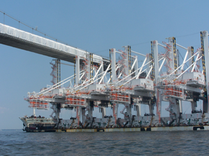 cranes being shipped under a bridge